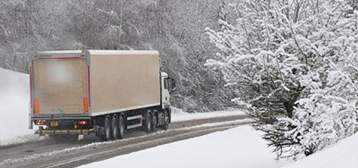 Lorry driving through the snow along a well-cleared road