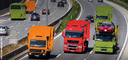 Red, amber and green heavy vehicles driving along a motorway