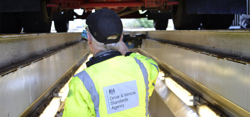 DVSA vehicle inspector underneath a lorry