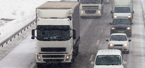 Lorries and cars on a snowy road