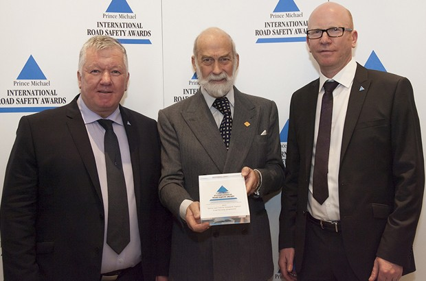 Prince Michael holding a Road Safety Award with DVSA's Ronald Arnott and Mark Horton