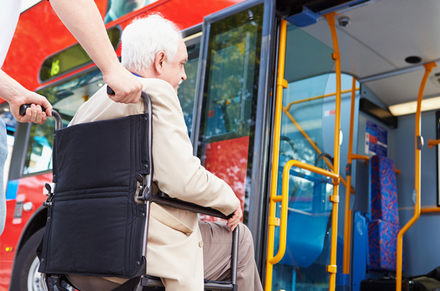 Man in wheelchair about to get on to a bus