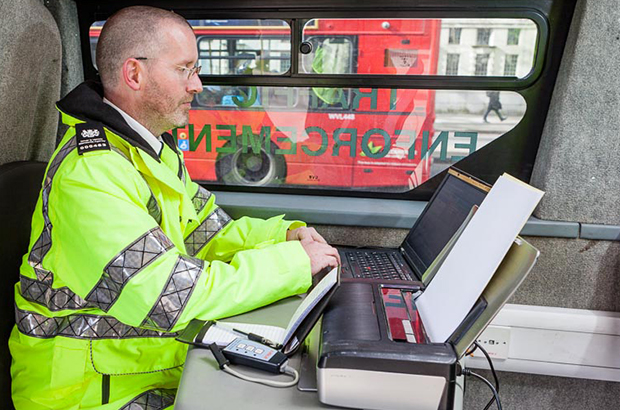 A DVSA traffic examiner at a computer checking vehicle records