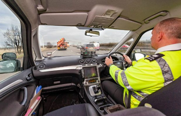 A DVSA enforcement officer driving a car on the motorway