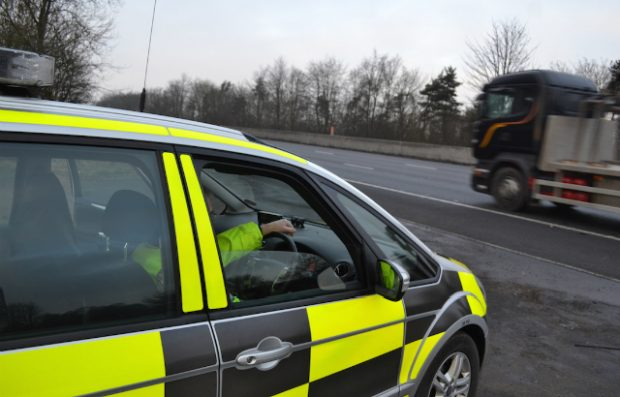 A DVSA enforcement vehicle stopped by the side of the road as a truck drives past