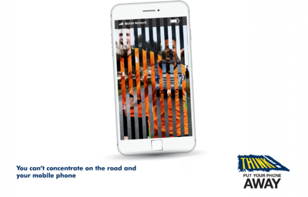 A mobile phone with two competing images - one of a football game and another of traffic.