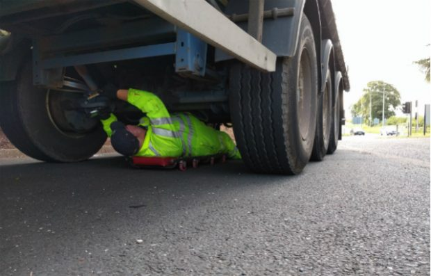 DVSAn enforcement officer checking under a lorry