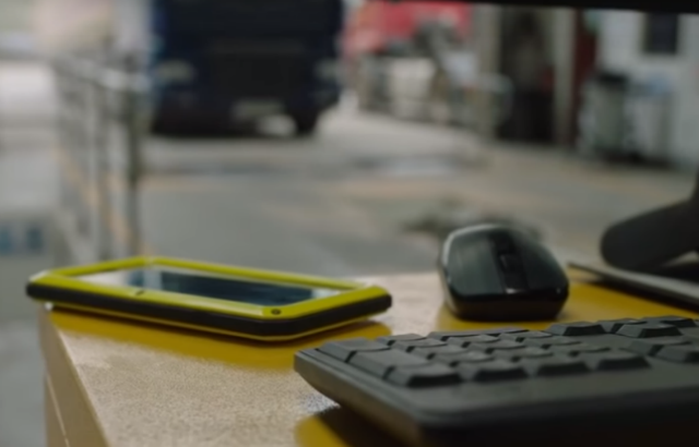 A mobile phone sitting on a desk next to a mouse and keyboard. A heavy vehicle testing pit in the background.