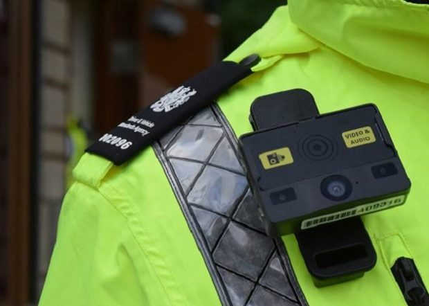 A body camera affixed to the chest of a DVSA officer in a high-vis jacket. The camera bears a sticker saying 'Video & Audio'