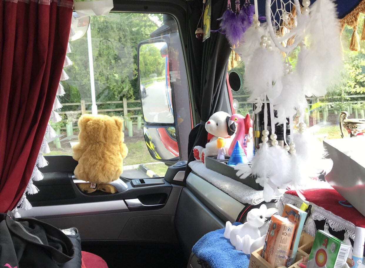 Cluttered lorry cab showing hanging toys, trinkets and fringed curtains