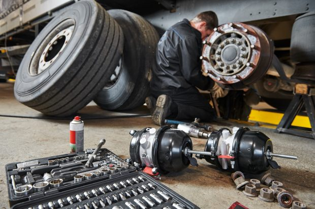 Truck repair service. Mechanic takes off tyre for brake replacement